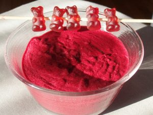 picture showing a bowl of blackcurrant mousse, decorated with blackcurrant gummybears