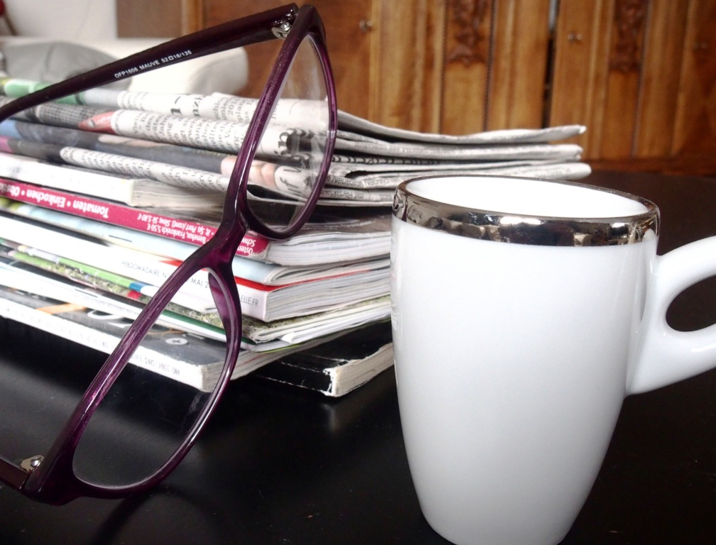 pile of magazines and newspapers with reading glasses and a cup of coffee to illustrate blackurrant press releases
