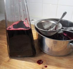bottle half filled with blackcurrant cordial with sieve and spoon beside the bottle