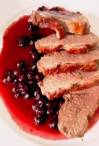 slices of duck fillet lying on a sauce blackurrants