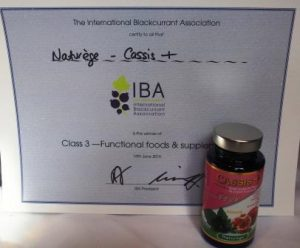 bottle of Cassis+ by Naturege standing in front of the award for functional foods from the blackcurrant contest 2016