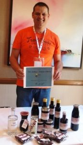 Heiko Danner standing behind a table displaying a huge range of blackcurrant products and holding an award for the overall winner at the blackcurrant contest 2016