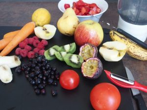 blackcurrants and several other fruits and vegetables with knife and blender for the preparation of smoothies