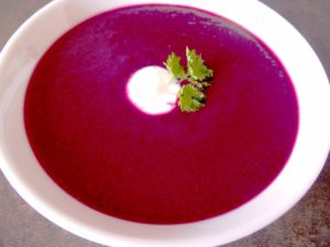 round shaped dish with blackcurrant gaspacho, decorated with a little bit of yogurt and parsley