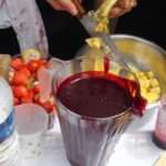 jug of exotic blackcurrant smoothie, someone cutting mangoes and strawberries in the background