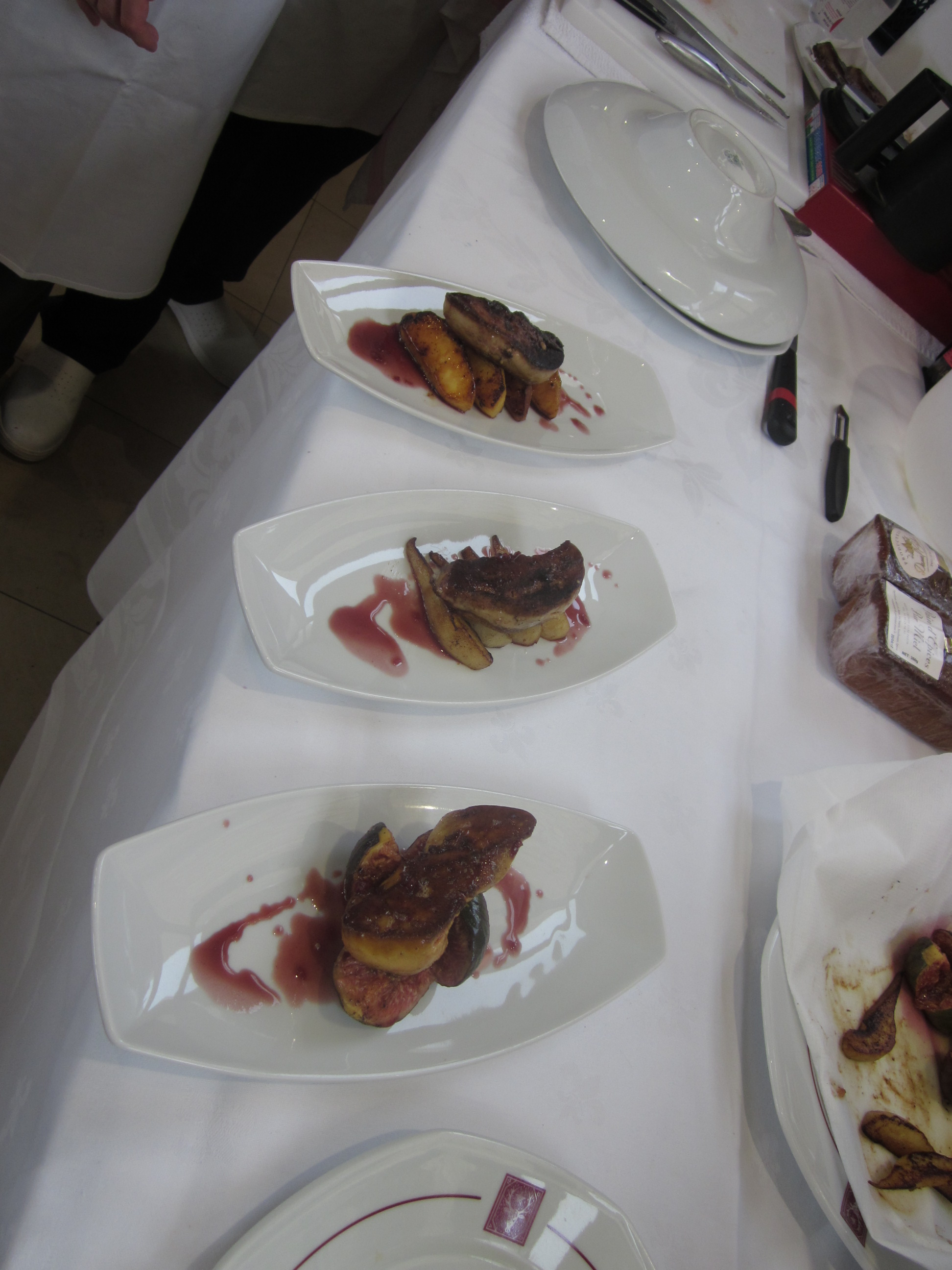 several plates with a piece of fried duck liver with cassis sauce around it