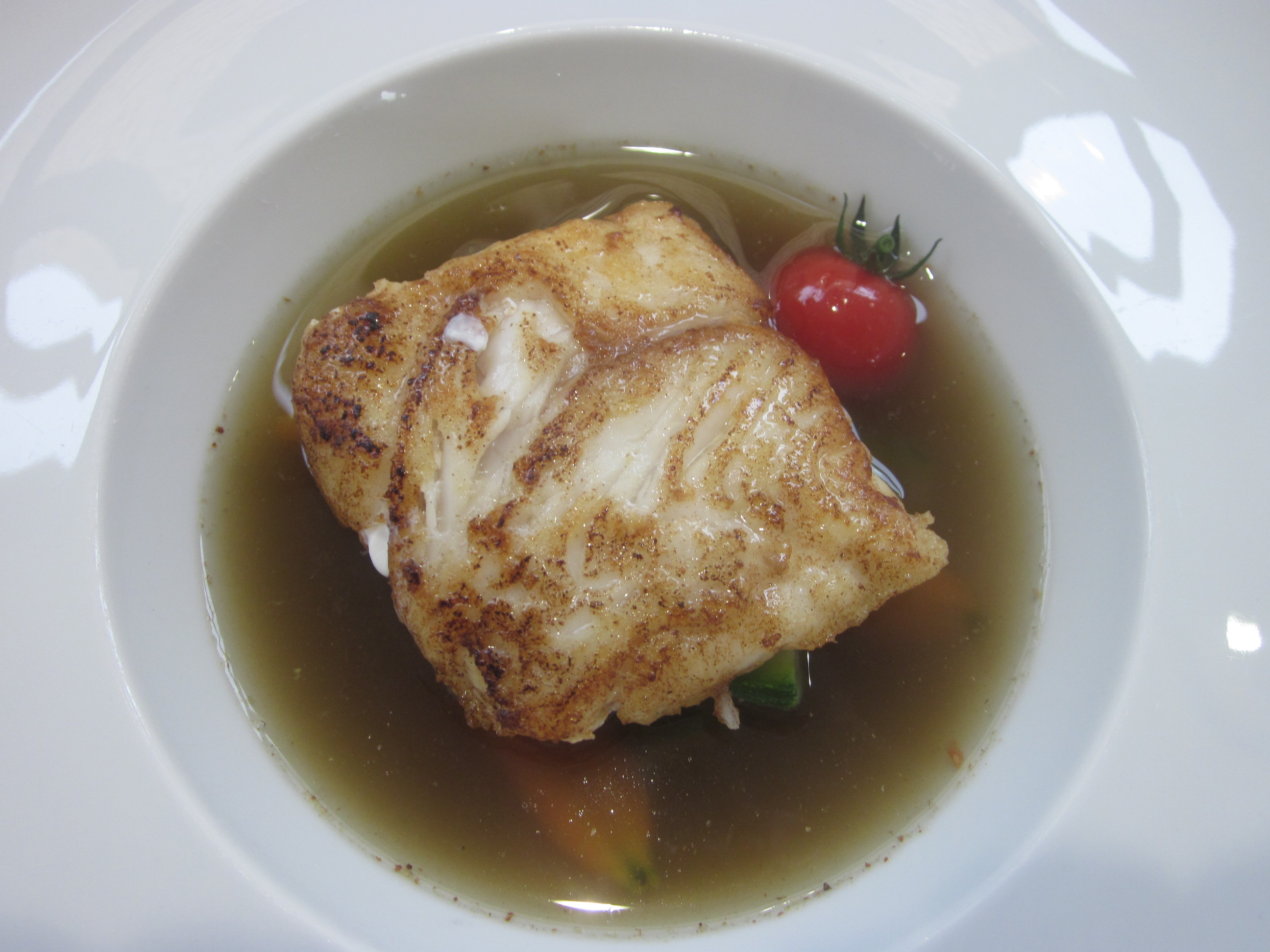 plate with a piece of hake and a tomato with a sauce in a fish stew with blackcurrant pepper