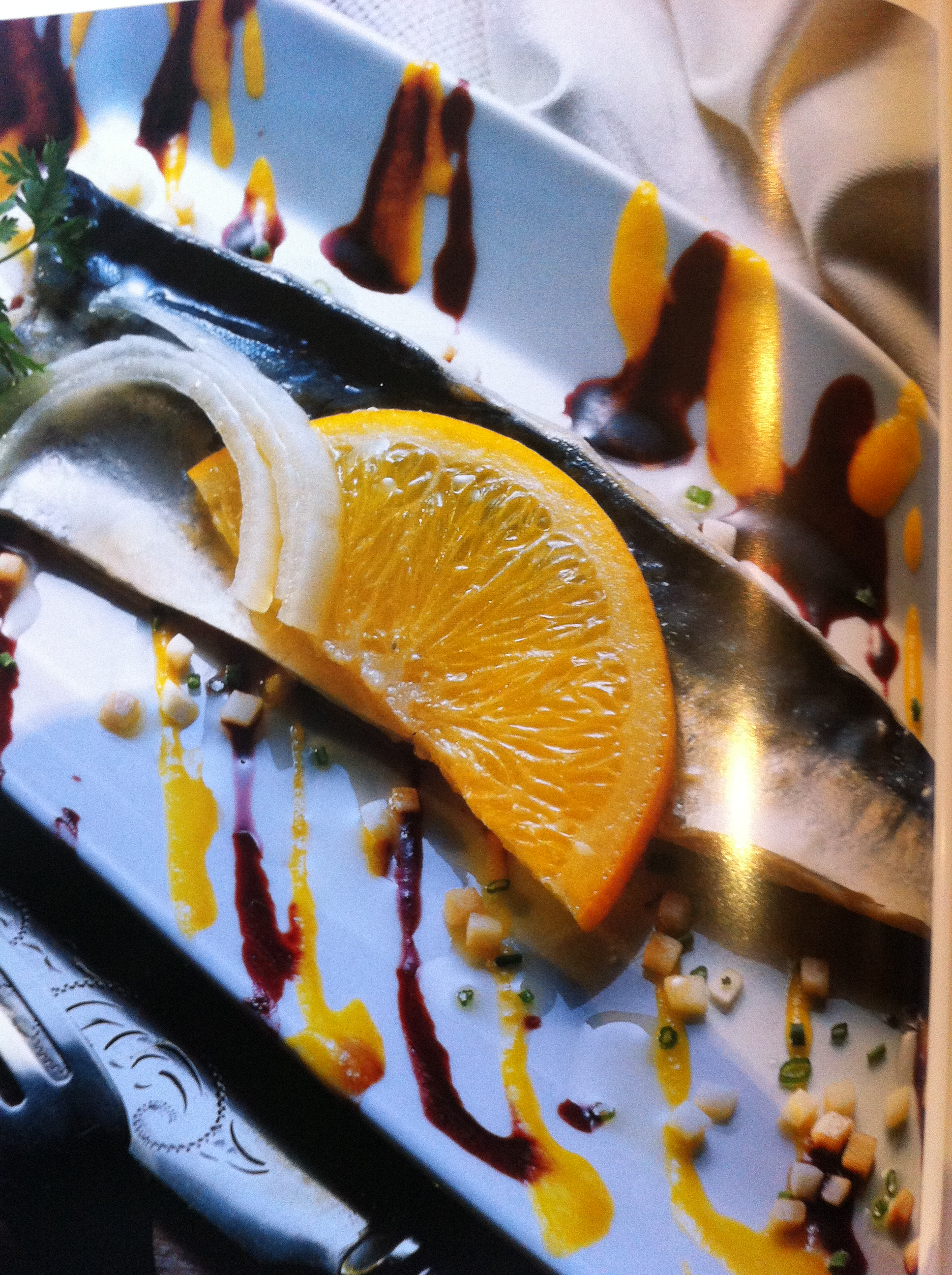 plate of mackerels with blackcurrant coulis and mandarin coulis, decorated with half a slice of orange