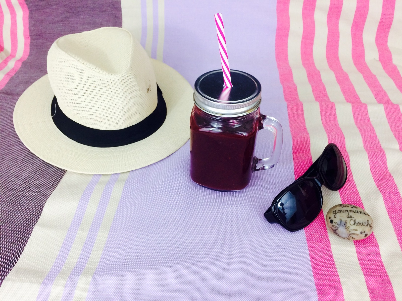 glass of energy blackcurrant smoothie with a hat and sunglasses lying beside