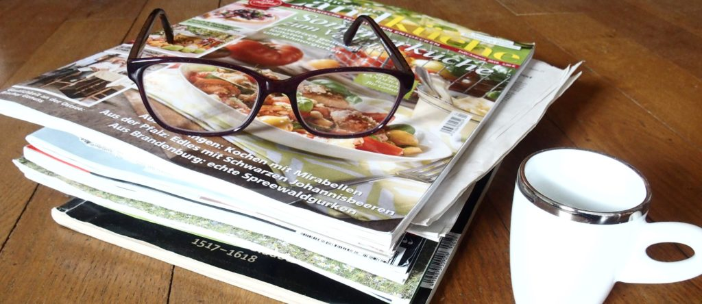 picture of magazines, a cup of coffee and reading glasses as a logo of the newsletter of the International Blackcurrant Association