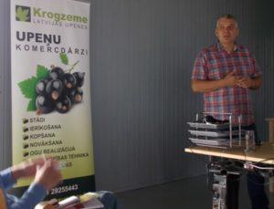 Andris Krogzems, standing beside a roll-up of Krogzeme farm