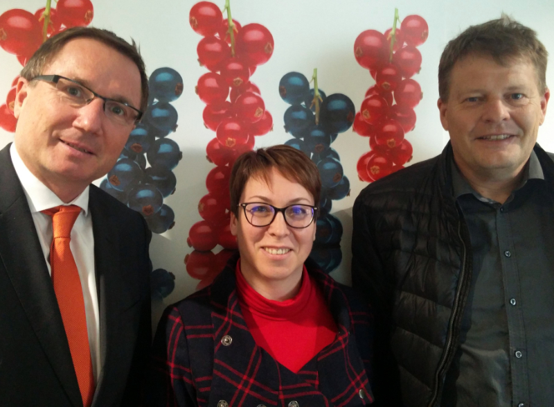 Franz Ennser (CEO Austria Juice), Stefanie Sharma (General Manager IBA) and Jens Holme Pedersen (president IBA) standing in front of a wall decorated with red and blackcurrants, illustrating an article about a meeting in Austria