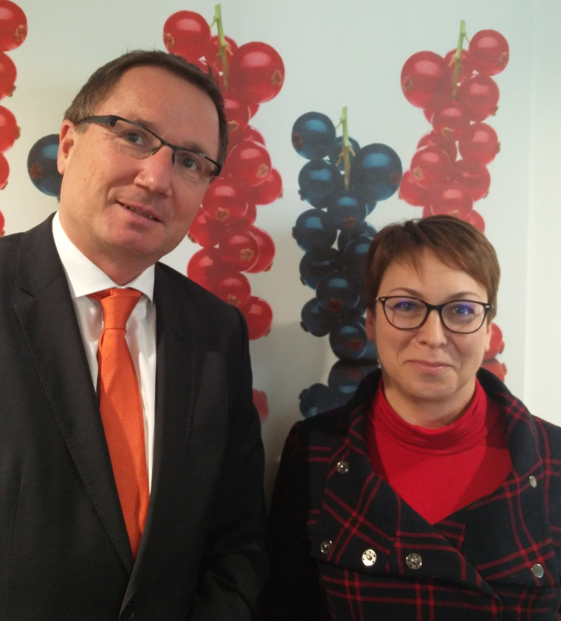 Franz Ennser (CEO Austria Juice), Stefanie Sharma (General Manager IBA) standing in front of a wall decorated with red and blackcurrants, illustrating an article about a meeting in Austria