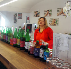 Gudrun Schriebl standing behind the bar of her farm shop Ribes, a row of different organic juice bottles in front of her