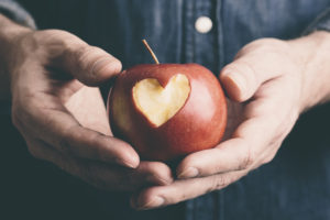 hands with apple, decorated with a heart, to illustrate engagement in sustainability